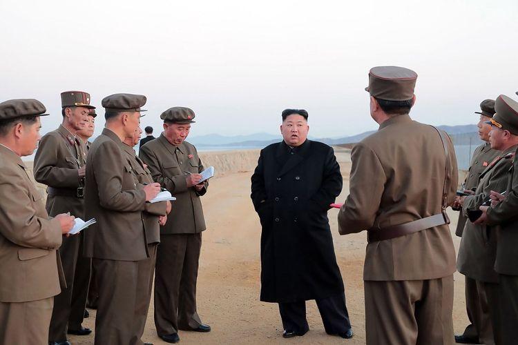 Pemimpin Korea Utara Kim Jong Un (bermantel hitam) memberi pengarahan kepada para pejabat militer setelah Korut mengklaim sukses mengujicoba senjata taktis berteknologi tinggi.