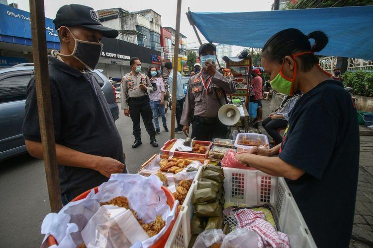 Petugas gabungan menginformasikan tentang peraturan berdagang kepada para pedagang makanan untuk berbuka puasa (takjil) di kawasan Bendungan Hilir, Jakarta, Jumat (24/4/2020). Pemprov DKI mengizinkan pedagang makanan dan minuman di kawasan tersebut untuk menjual takjil selama bulan Ramadhan dengan ketentuan tetap mengikuti aturan Pembatasan Sosial Berskala Besar (PSBB). ANTARA FOTO/Rivan Awal Lingga/wsj.