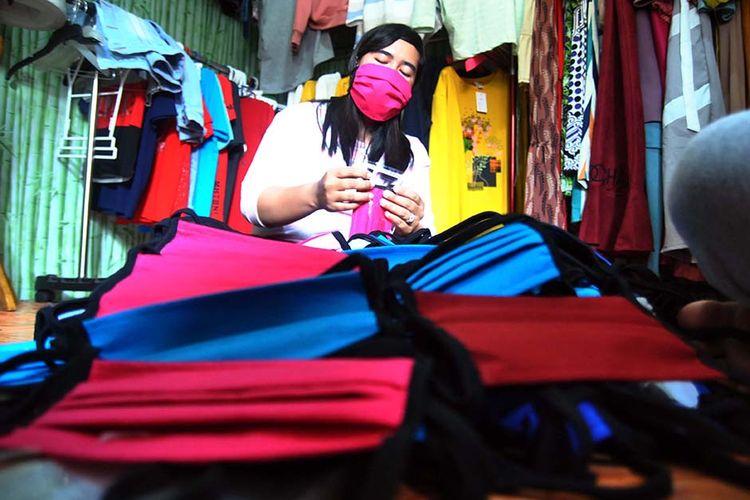Pekerja menyelesaikan pembuatan masker dari bahan kain katun combed di Kaos Bogor 767 Teguh Printing, Sindang Barang Pilar, Kelurahan Bubulak, Kota Bogor, Jawa Barat, Sabtu (28/3/2020). Permintaan pembuatan masker di jasa konveksi kaos dan jaket di tempat tersebut mengalami peningkatan mencapai sedikitnya 2 ribu masker sementara kapasitas produksi hanya mencapai 50 lusin setiap harinya untuk memenuhi kelangkaan masker dan harga yang tinggi akibat pandemi virus Corona (COVID-19).