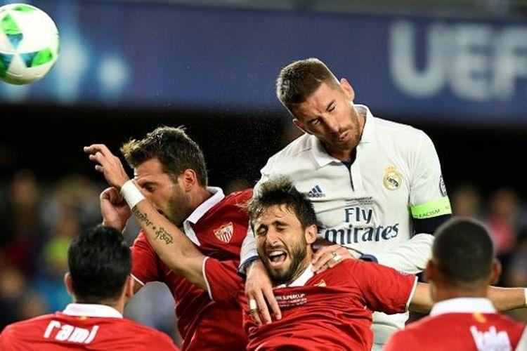 Bek sekaligus kapten Real Madrid, Sergio Ramos (atas), berduel dengan bek Sevilla, Nicolas Pareja (bawah), dalam laga Piala Super Eropa 2016 di Stadion Lerkendal, Trondheim, Norwegia, pada Selasa (9/8/2016) atau Rabu dini hari WIB.