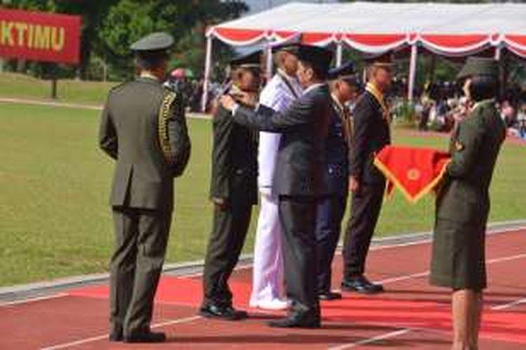 Presiden Joko Widodo menyematkan anugerah Adhimakayasa kepada Tri Ageng Widhi Nugroho, salah satu taruna terbaik lulusan Akademi TNI-Polri 2016, di lapangan Sapta Marga Akademi Militer Magelang, Selasa (26/7/2016).