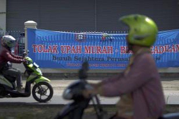 Pengendara sepeda motor melintas di depan spanduk