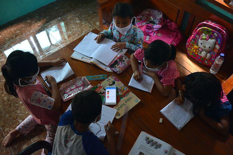 Foto dirilis Rabu (16/9/2020), memperlihatkan sejumlah siswa SDN Marmoyo, mengerjakan tugas dengan berkelompok menggunakan gawai secara bergantian di rumah warga Desa Marmoyo, Kecamatan Kabuh, Kabupaten Jombang, Jawa Timur. Pembelajaran secara daring selama pandemi Covid-19 ini memunculkan masalah tersendiri bagi anak-anak yang tinggal di wilayah pelosok Jombang yang tidak bisa mengakses jaringan internet.