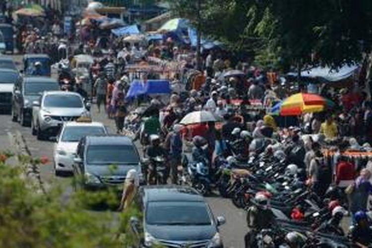 Lalu lintas tersendat di ruas jalan di depan pusat perdagangan Pasar Senen, Jakarta, Senin (28/4/2014). Pascakebakaran beberapa hari lalu, ratusan pedagang terpaksa berjualan dengan memakan badan jalan sehingga menambah keruwetan jalan di sekitar pasar.