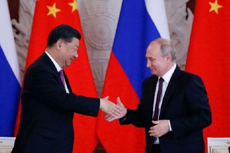 Presiden China Xi Jinping ketika berjabat tangan dengan Presiden Rusia Vladimir Putin saat berkunjung ke Moskwa pada Rabu (5/6/2019).