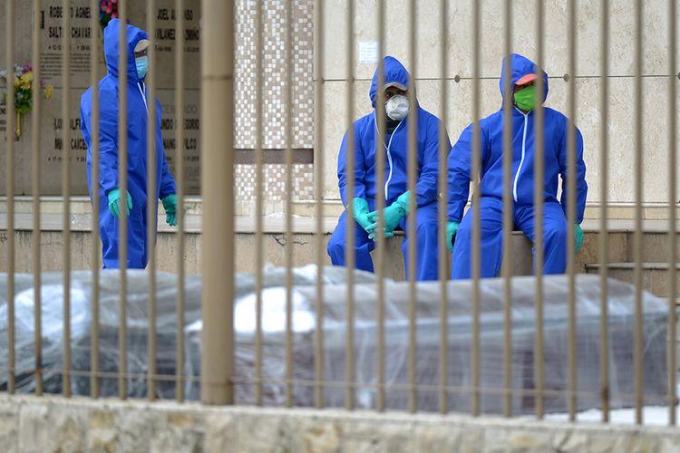 Sejumlah petugas dengan mengenakan alat pelindung diri (APD) duduk di samping barisan peti mati di sebuah pemakaman di Guayaquil, Ekuador, di tengah lonjakan kasus virus corona di wilayah tersebut, Rabu (1/4/2020). Otoritas Ekuador dalam beberapa hari terakhir telah mengumpulkan setidaknya 150 jenazah dari jalan-jalan dan rumah para warga di Kota Guayaquil, di tengah lonjakan kasus virus corona di wilayah tersebut.
