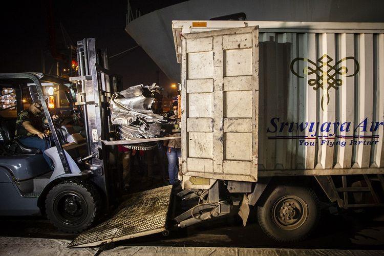Petugas mengangkat bagian pesawat Sriwijaya Air SJ-182 ke dalam mobil di Dermaga JICT II, Pelabuhan Tanjung Priok, Jakarta Utara, Kamis (21/1/2021). Tim SAR gabungan menyerahkan barang-barang temuan dari jatuhnya pesawat Sriwijaya Air SJ-182 kepada Komite Nasional Keselamatan Transportasi (KNKT) untuk dilakukan investigasi lebih lanjut. ANTARA FOTO/Dhemas Reviyanto/foc.