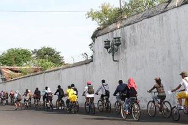 Mengayuh sepeda melewati kompleks Pura Mangkunegaran.