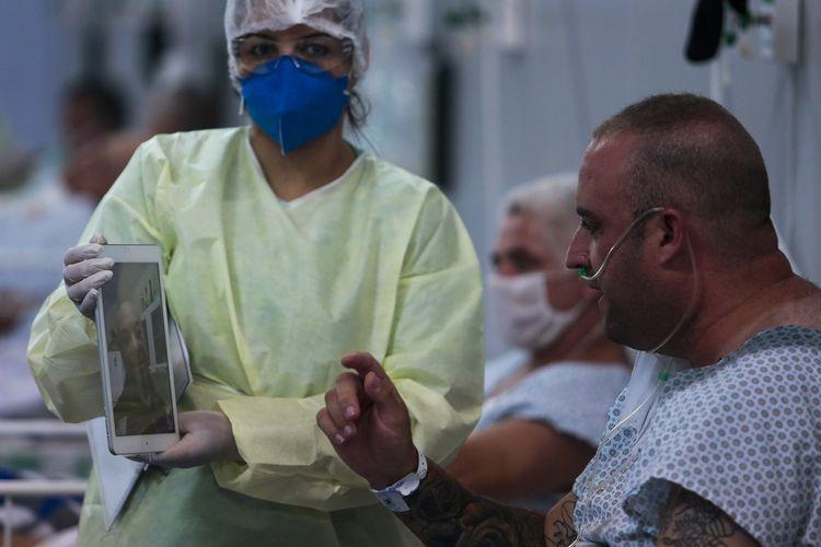 Seorang pasien yang terinfeksi virus corona berbicara dengan keluarganya melalui panggilan video di rumah sakit lapangan yang didirikan di gim Santo Andre, Sao Paulo, Brasil, pada 11 Mei 2020.