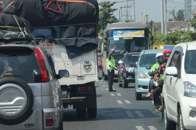 Petugas Satlantas Polres Kebumen mengatur arus kendaraan di jalur selatan Jawa, Senin (11/6/2018).