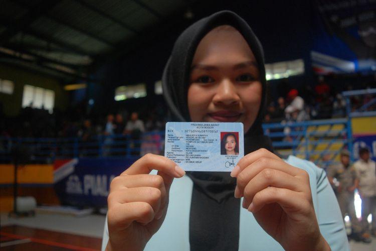 Seorang warga Kota Bogor menunjukkan e-KTP yang diterimanya dalam acara pembagian KTP elektronik secara serentak di Gedung Hall A GOR Pajajaran, Minggu (5/11/2017)