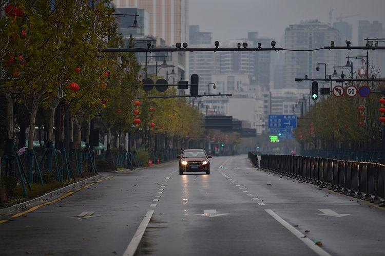 Sebuah mobil melaju sendiri di jalanan kota Wuhan, China, yang sepi akibat wabah virus corona yang mematikan, Minggu (26/1/2020).