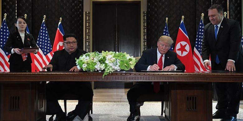 Presiden AS Donald Trump dan pemimpin Korea Utara Kim Jong Un menandatangani kesepakatan usai melakukan pertemuan di Hotel Capella, Singapura, Selasa (12/6/2018). Penandatanganan ini disaksikan Menlu AS Mike Pompeo dan adik Kim Jong Un, Kim Yo Jong.