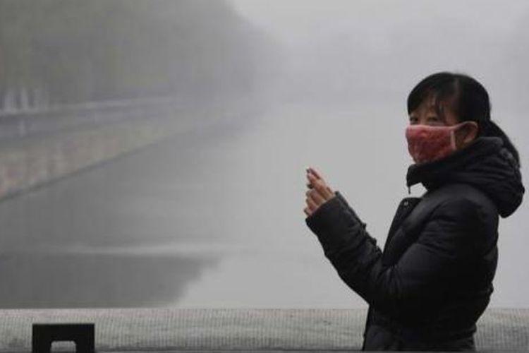 Seorang wanita mengenakan masker wajah saat mengambil foto di sekitar Forbidden City yang diselimuti oleh kabut asap polusi udara, Selasa, 8 Desember 2015. Pemerintah Kota Beijing, Senin sore, untuk pertama kalinya dalam sejarah menaikan status kabut menjadi darurat berstatus ?berwarna merah? yang merupakan status darurat paling tinggi.