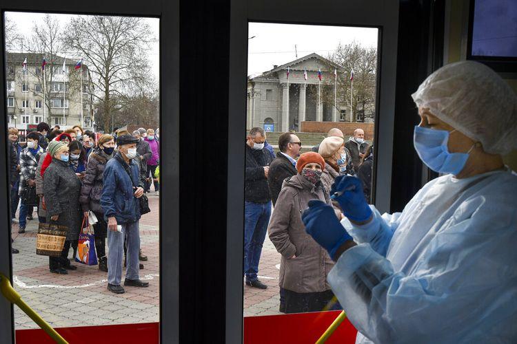 Seorang pekerja medis Rusia menyiapkan suntikan vaksin virus corona Sputnik V Rusia di pusat vaksinasi mobile di Simferopol, Krimea, Selasa (13/4/2021)