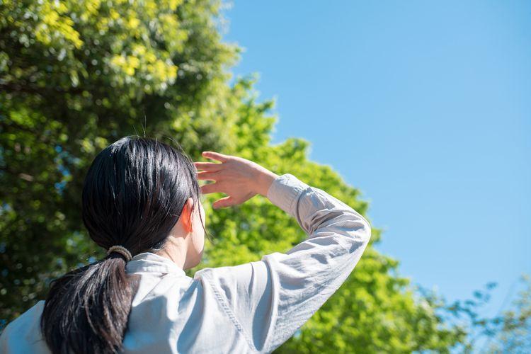 Seorang perempuan menggunakan tangannya untuk menahan sinar matahari agar tidak kepanasan di siang hari yang terik