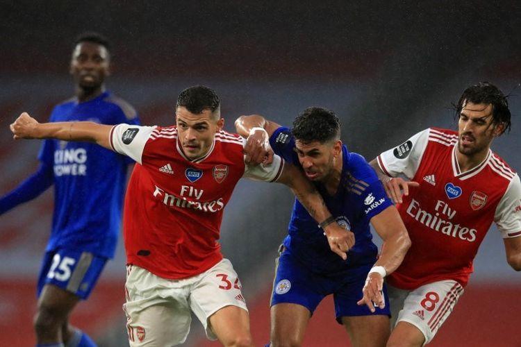 Granit Xhaka (kiri) berduel dengan Ayoze Perez (tengah) pada laga Arsenal vs Leicester City di Stadion Emirates dalam lanjutan pekan ke-34 Premier League, kasta teratas Liga Inggris, Selasa 7 Juli 2020.