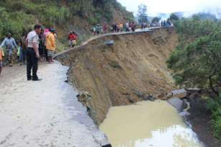 Jalan Trans Papua di Kecamatan Poga, Kabupaten Tolikara  yang putus karena terkena longsor pada Sabtu (13/2/2016) kemarin. Longsor mengakibatkan akses jalan dari Wamena ke Tolikara terputus.