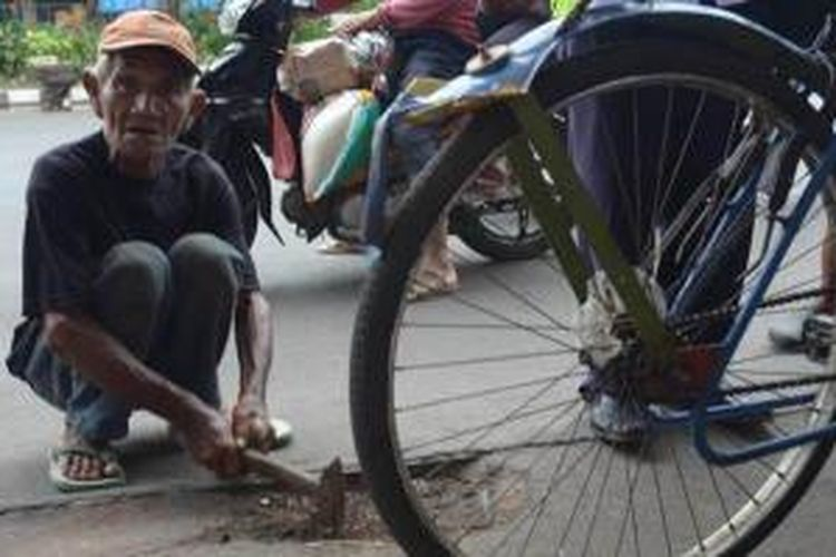 Abdul Sukur, tukang becak yang secara sukarela menambal jalan yang rusak di wilayah Surabaya.