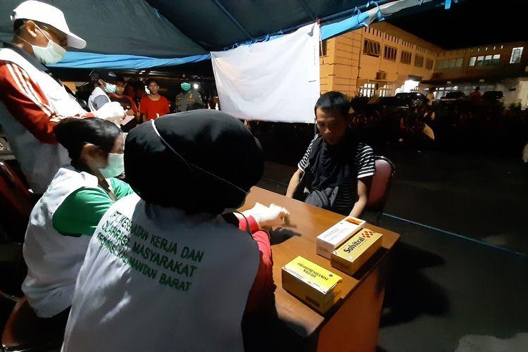 Sejumlah pekerja migran Indonesia yang dideportasi yang dideportasi dari Malaysia sedang antre pemeriksaan kesehatan oleh petugas Dinas Sosial dan Ketenagakerjaan Kalbar, Sabtu (21/3/2020).