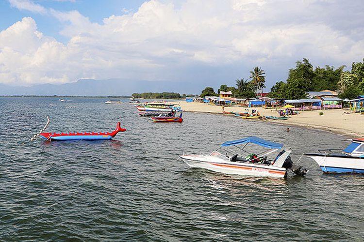 Wisatawan menikmati Danau Toba di Pantai Pasir Putih Lumban Bulbul, Kecamatan Balige, Kabupaten Toba Samosir, Sumatera Utara, Jumat (9/6/2017).