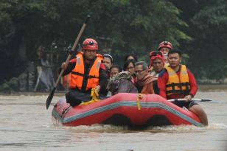Warga korban banjir di Kampung Pulo, Jatinegara, Jakarta Timur, dievakuasi menggunakan perahu karet ke tempat pengungsian, Senin (13/1/2014). Sejumlah wilayah di Jakarta terendam banjir akibat curah hujan yang tinggi dan air kiriman dari Bogor. TRIBUNNEWS/HERUDIN
