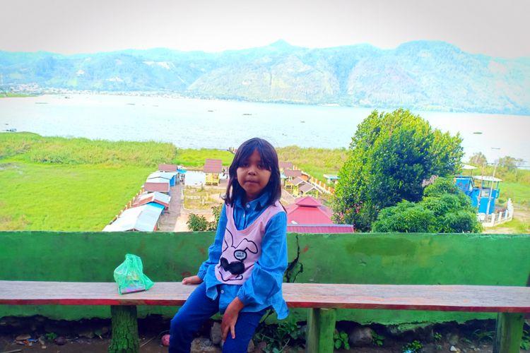 Seorang anak berfoto dengan latar belakang danau di Dermaga Dedalu, Desa Dedalu, Kecamatan Lut Tawar, Kabupaten Aceh Tengah