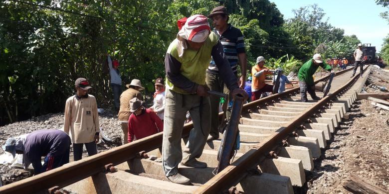 Sejumlah petugas saat memperbaiki rel kereta yang jebol karena diterjang banjir di Dusun Botokan, Desa Tambakrejo, Kecamatan Kraton, Kabupaten Pasuruan, Jumat (1/7/2016)