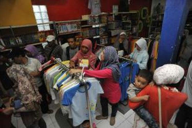 Pemudik berbelanja kaos di gerai industri kaos Dagadu, Jalan Pakuningratan, Yogyakarta, Jumat (24/8/2012). Kaos hasil industri kreatif merupakan salah satu komoditi yang banyak dicari pemudik selama berada di Yogyakarta.
