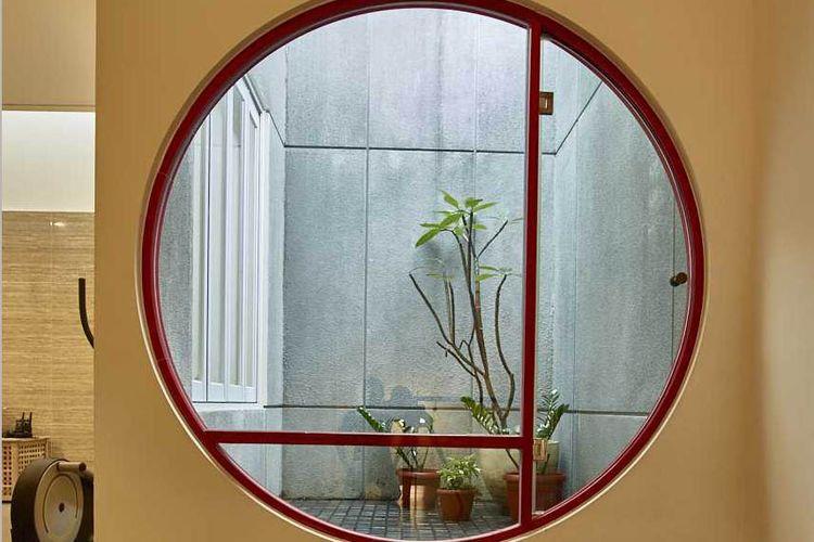 Jendela bulat ke arah taman Tena House Mekar Wangi Karya Dinardithen Studio
