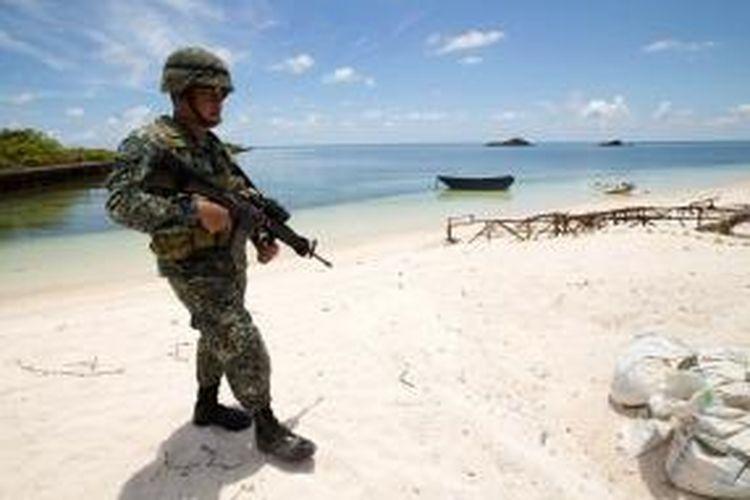 Seorang prajurit Filipina berjaga di pantai Pulau Pagasa di gugusan Kepulauan Spratly di Laut China Selatan yang disengketakan.