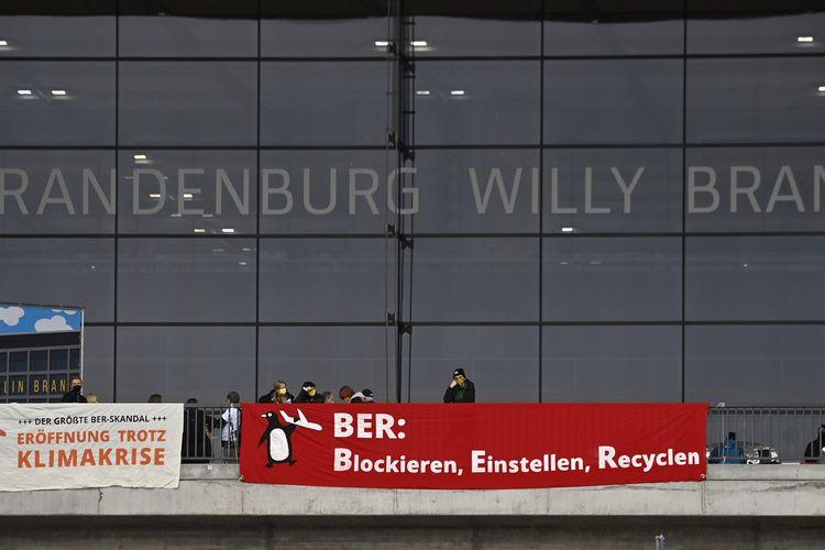 Aktivis lingkungan hidup memasang spanduk bertuliskan dibuka walau krisis iklim (kiri) dan BER: Block, Erase, Recycle (kanan) di depan terminal utama bandara Berlin Brandenburg Willy Brandt, jelang pembukaannya pada 31 Oktober 2020.