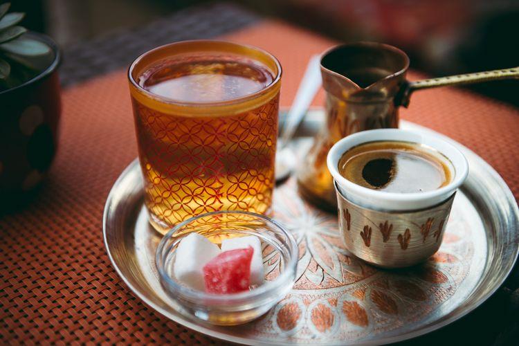 Ilustrasi tata cara minum kopi ala Bosnia, dengan segelas kopi, air mineral, alat perebus kopi, gula blok, serta manisan turkish delight