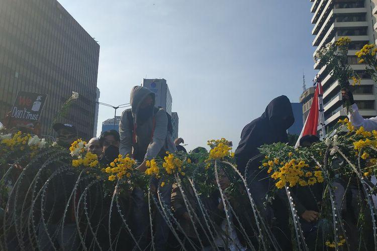 Sejumlah bunga diletakkan di pagar kawat berduri yang menghalau massa aksi di depan Bawaslu sebagai simbol duka cita atas insiden yang terjadi di Tanah Abang pada Rabu (22/5/2019).