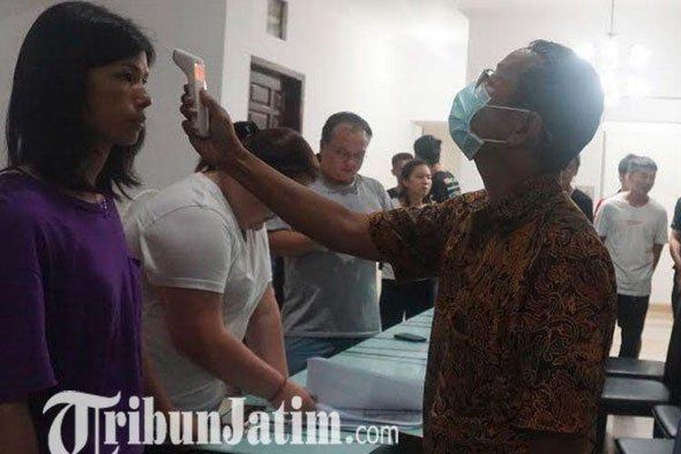 Petugas Dinas Kesehatan Tulungagung memeriksa suhu tubuh 16 WNA yang ditemukan di Tulungagung.