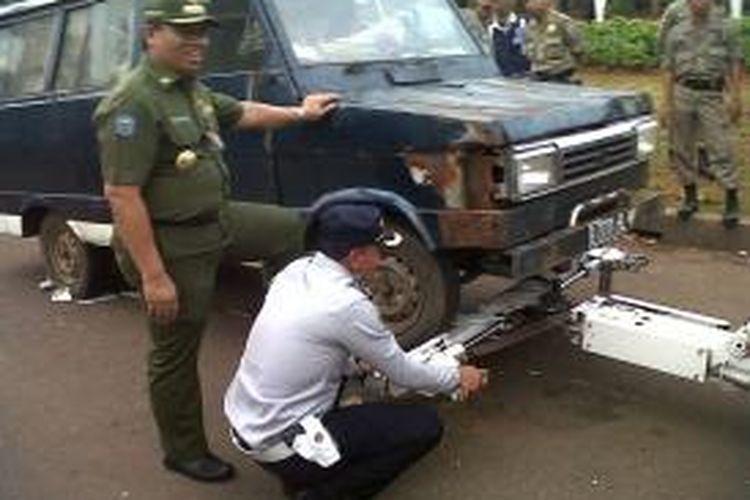Salah satu mobil PKL yang terparkir di Monas diderek petugas.