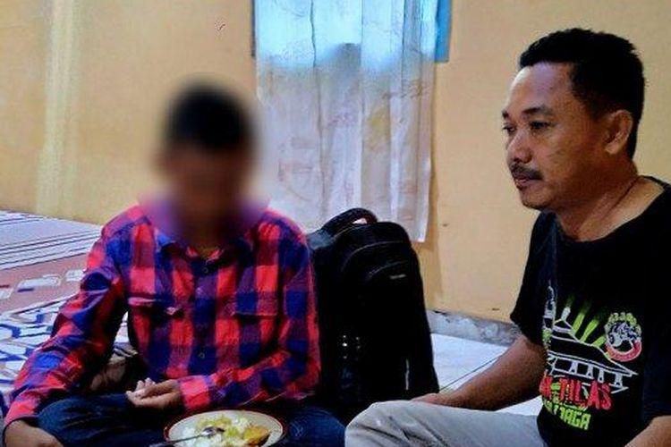 Bocah yatim piatu PR duduk di samping Nur Kholis, seorang ketua RT di jalan Blancir Raya, Jumat (21/2/2020).