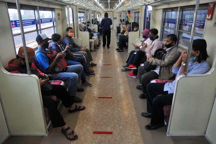 Sejumlah penumpang menggunakan masker dan duduk berjarak di dalam gerbong KRL Commuter Line, Stasiun Bogor, Jawa Barat, Rabu (15/4/2020). Pada hari pertama penerapan Pembatasan Sosial Berskala Besar (PSBB) di wilayah Kota Bogor, pengguna KRL Commuter Line masih berjalan normal dengan setiap jadwal keberangkatan memiliki jeda sekitar 5 hingga 10 menit dan pembatasan jumlah penumpang pada setiap gerbong.
