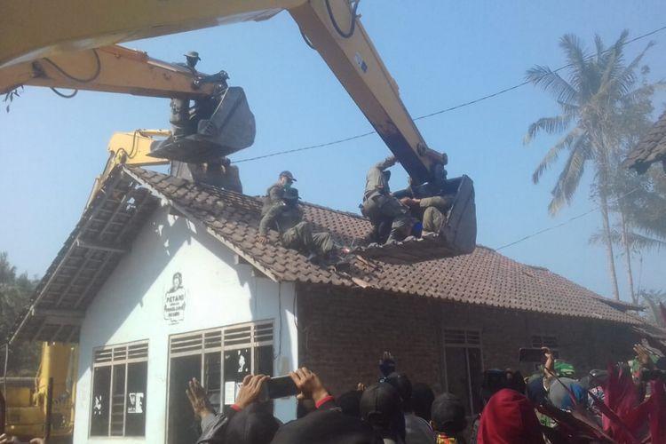 : Empat Satpol PP dan seorang polisi bergulat dengan Sumiyo yang bertahan di atas genteng rumah. Ia tak mau rumahnya digusur.