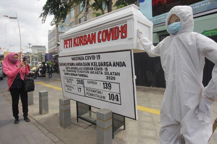 Warga memotret papan informasi tentang jumlah warga terpapar COVID-19 di kawasan Kemang, Jakarta, Jumat (21/8/2020). Papan informasi itu menjadi salah satu bentuk kampanye baru untuk mengingatkan masyarakat akan bahaya virus corona baru (COVID-19). ANTARA FOTO/Reno Esnir/wsj.  *** Local Caption ***