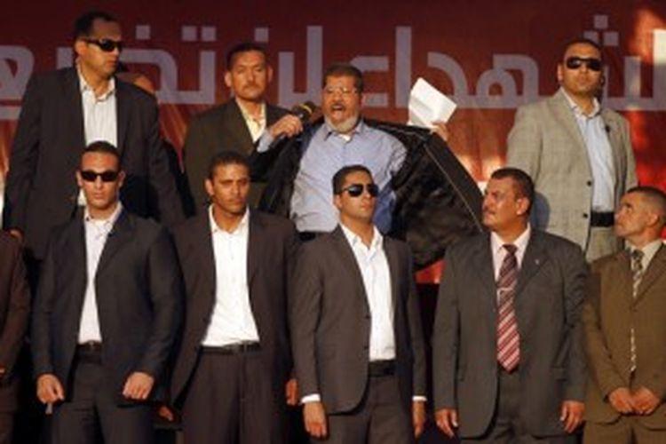 FILE - Mesir Presiden Mohammed Morsi (tengah) membuka jaketnya untuk menunjukkan bahwa dia tidak memakai rompi pelindung saat ia memberikan pidato di Alun-alun Tahrir di Kairo, Mesir, 29 Juni 2013.