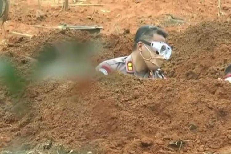 Kepala Satuan (Kasat) Shabara Polrestabes Palembang AKBP Sonny saat membantu menggali makam standar Covid-19 di Kecamatan Gandus, Palembang, Jumat (22/5/2020).