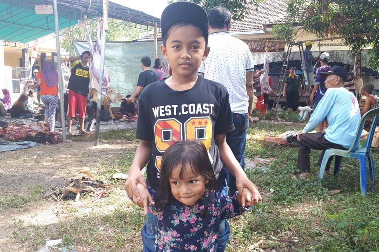 Al (9) dan adiknya di tempat penyembelihan kambing kurban di Banyuwangi. Al sudah berkurban kambing sejak dia masih berusia 7 tahun