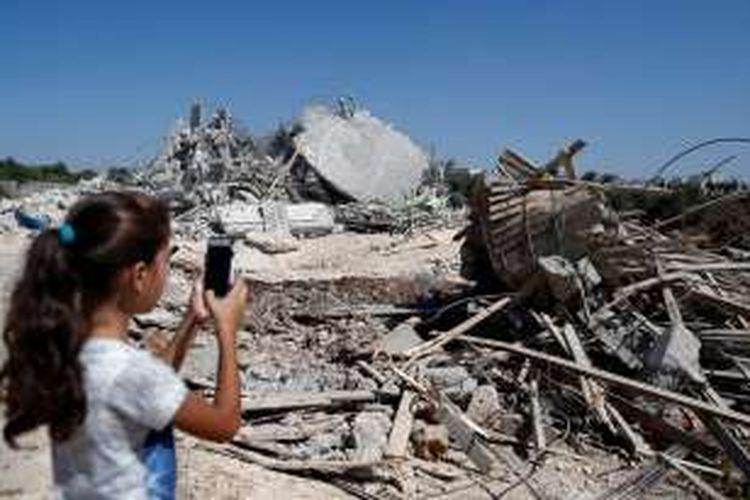 Dengan menggunakan telepon genggam, seorang bocah Palestina mengadikan sisa-sisa rumahnya di Qalandiya, Jerusalem yang dihancurkan pemerintah Israel, Selasa (26/7/2016).