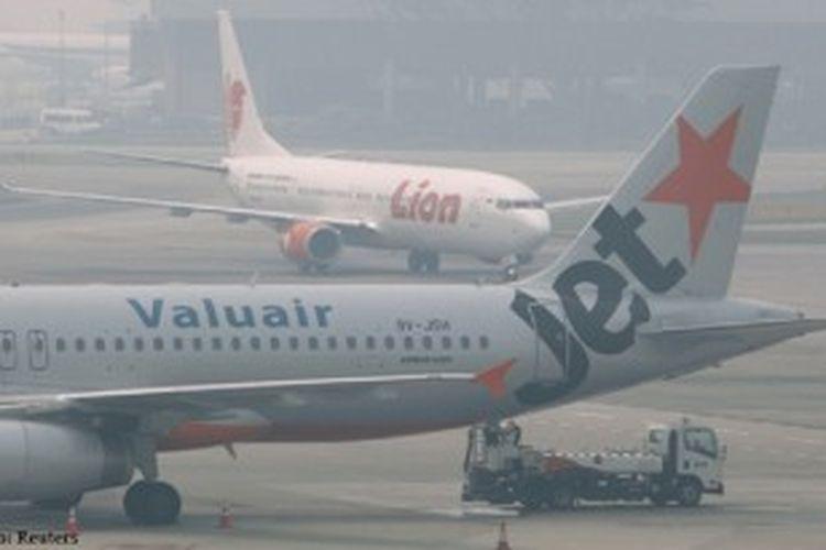 Terlihat pesawat Jetstar dan Lion Air di bandara Changi yang diselimuti kabut asap