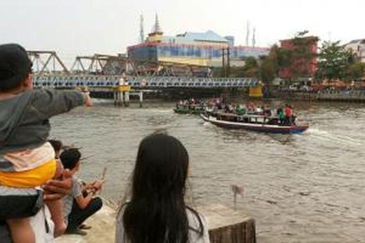 Di dekat patung, para pengunjung bisa bersantai menikmati makanan di tepi sungai Martapura sembari melihat-lihat kendaraan sungai yang melintas.