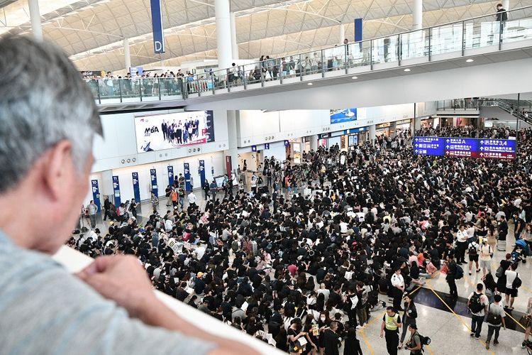 Seorang pengunjung melihat massa pengunjuk rasa yang melakukan aksi duduk di aula kedatangan Bandara Internasional Hong Kong, Jumat (9/8/2019).