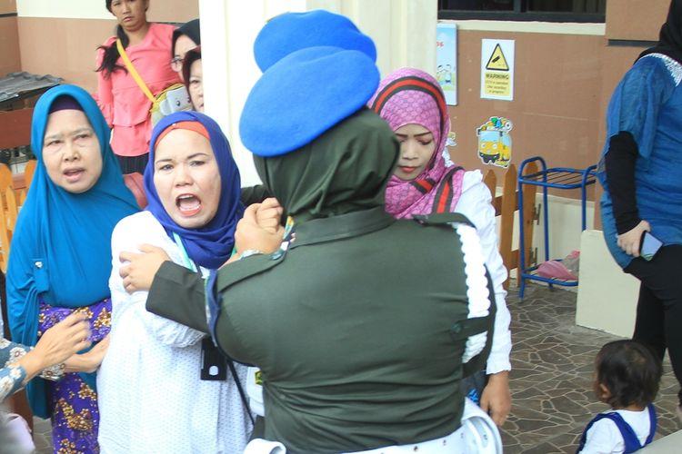 Suhartini ibu dari Fera Oktaria (21) yang merupakan korban pembunuhan serta mutilasi oleh terdakwa Prada DP mengamuk di depan ruang sidang Pengadilan Militer I-04 Palembang, Kamis (29/8/2019).