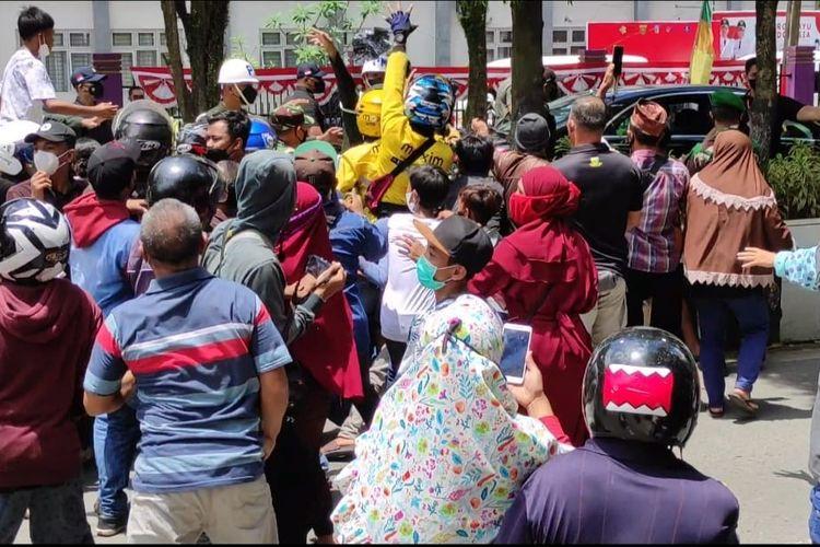 Kerumunan warga berebut baju kaos dari Jokowi di Jalan Pahlawan, Samarinda, Kaltim, Selasa (24/8/2021).