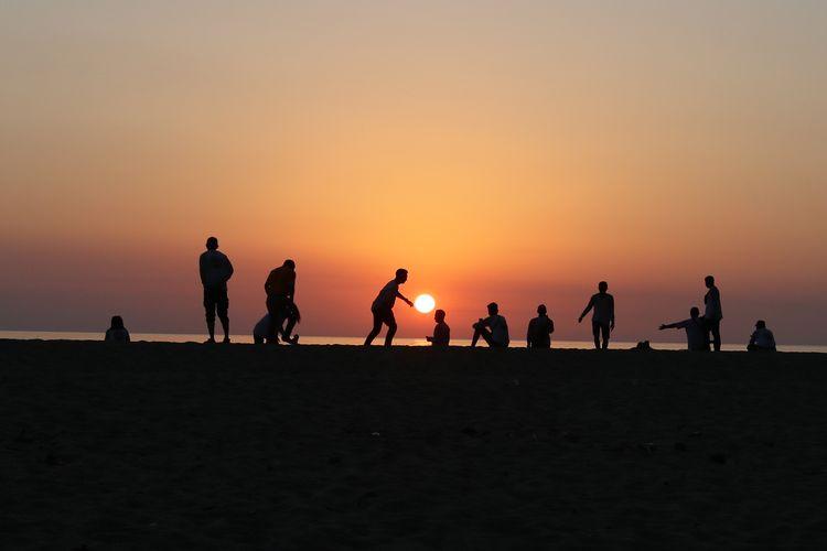 Pelancong menikmati sunset yang terbenam